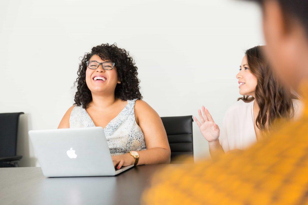 woman laughing at laptop in meeting