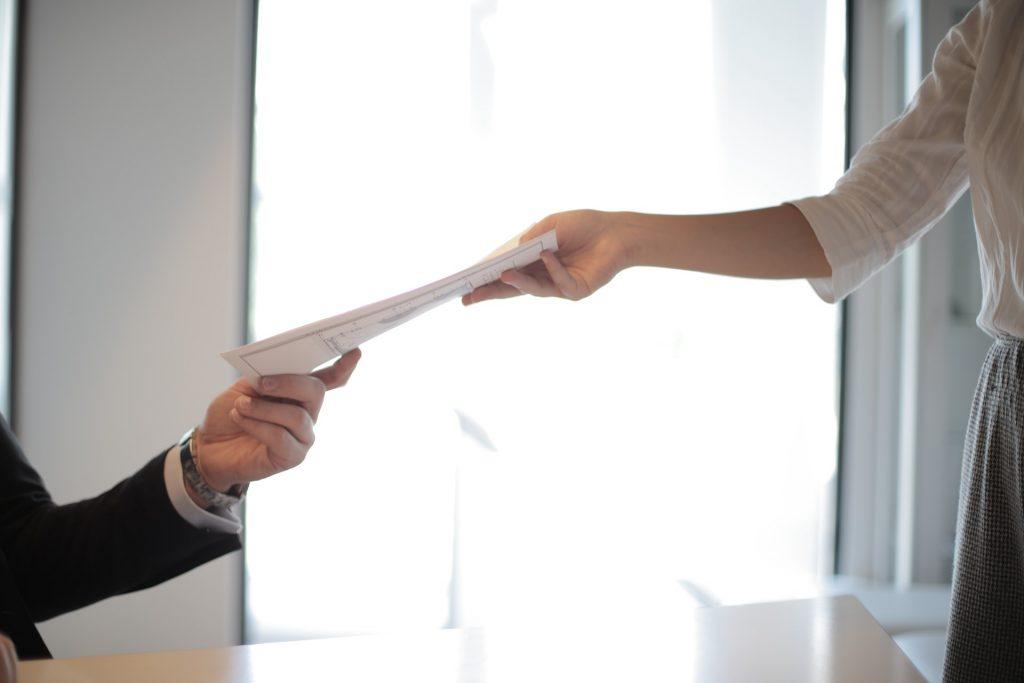 woman handing man resume